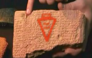 Tablilla de barro con escritura cuneiforme, donde se supone que el dedo señala la palabra cerveza (superpuesto en rojo).
